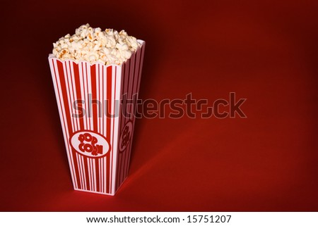 Buttered Popcorn in classic bucket on red background - stock photo