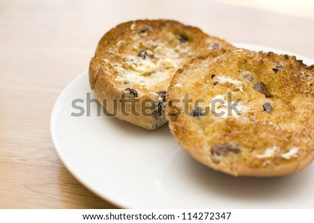 Buttered, toasted teacake on white plate - stock photo