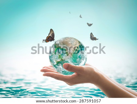 Butterfly drinking pure water from green planet on women hand w/ blurred nature background wavy water surface: CSR Save clean world water environment concept: Elements of this image furnished by NASA - stock photo