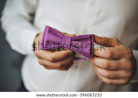 butterfly of violet color on a neck at the man. Man wears purple, purple bow-tie. The bridegroom going to the wedding. Wedding morning. The man straightens his tie.  - stock photo