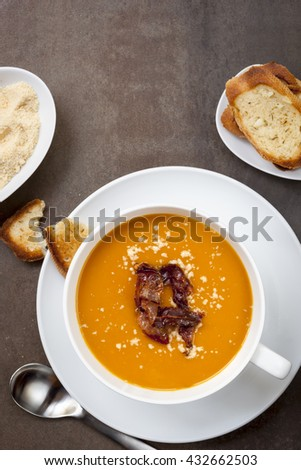 Butternut pumpkin soup, with crispy pancetta, parmesan and garlic bread.  Top view, over slate. - stock photo