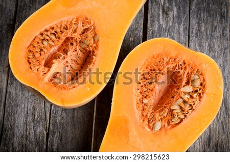 Butternut squash cut in half on a wooden surface - stock photo