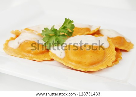Butternut Squash Ravioli with Garlic Herb Sauce and a side of Broccoli (focus on front edge of food) - stock photo