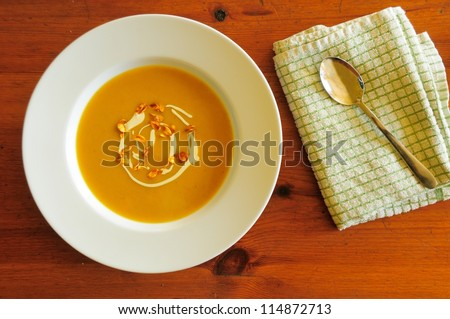 Butternut squash soup in clean white bowl on wooden table. Soup garnished with cream and spiced caramelised seeds. - stock photo