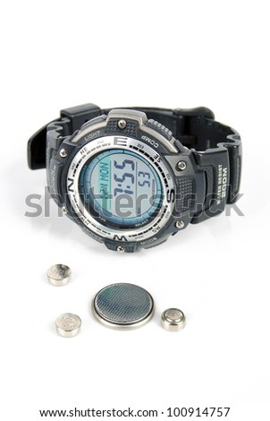 Button battery and wrist watch - stock photo