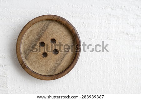 button on a wooden table, from above - stock photo