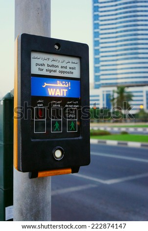 Button on the pedestrian crosswalk in Sharjah with blurred buildings and road in the background                          - stock photo