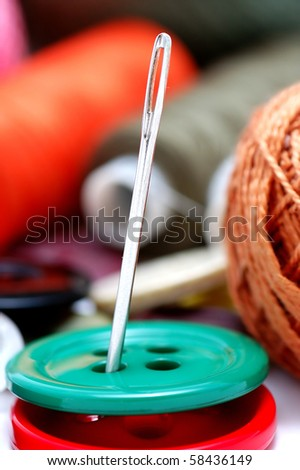 Buttons and threads with a needle close up on a white background - stock photo