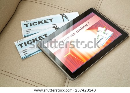 Buy cinema Tickets online with your mobile device or Tablet PC on the sofa.  - stock photo