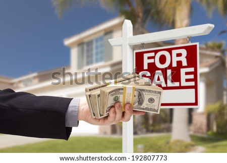Buyer Handing Over Cash for House with Home and For Sale Real Estate Sign Behind. - stock photo