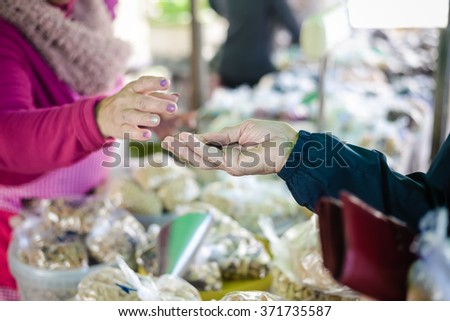 Buyer's and seller's hands on colorful marketplace background outdoors. Picture of marketplace with different products.  - stock photo