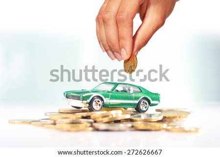 Buying car. Green car and coins over light background. - stock photo