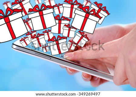 buying christmas presents by smartphone with drawn gift boxes on blue background - stock photo