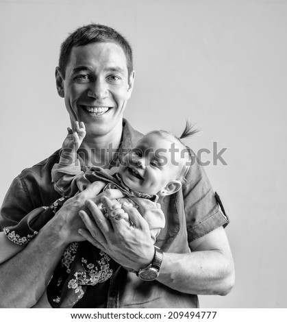 BW portrait of father playing with his daughter holding her in his arms. - stock photo