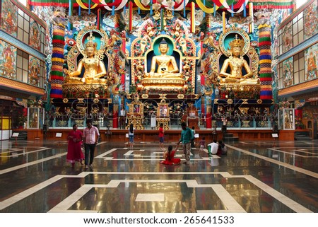BYLAKUPPE, INDIA - MAR 27, 2015 : Local tourists visit the Namdroling Monastery after prayer on March 27, 2015 in Bylakuppe, India. Bylakuppe second largest Tibetan refugee settlements in India. - stock photo