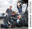 Bystanders checking up and providing first aid to an injured bleeding driver after a car crash. A man is taking pictures - stock photo