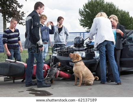 Bystanders creating amateur news casts and providing first aid to the victims of an accident between a motorcycle and a car - stock photo