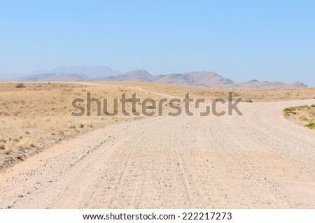 C14 road near Kuiseb Canyon, Namibia with Gamsberg mountain in the distance  - stock photo
