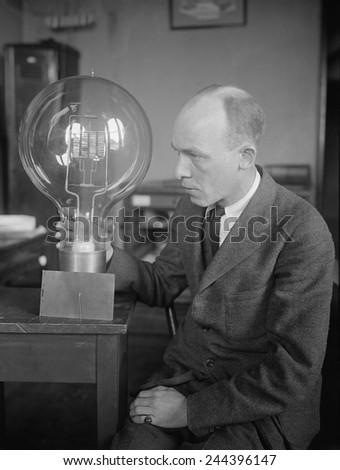 C.W. Mitman, Head Curator, Department of Engineering and Industries of the Smithsonian Institute, holds a giant light bulb. For contrast a midget bulb is placed beside it. March 1923. - stock photo
