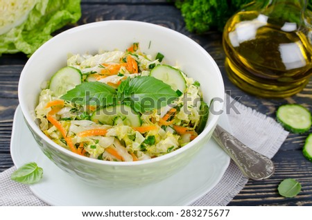 Cabbage salad with cucumber and carrots. Salad and vegetables on wooden table - stock photo