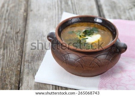 Cabbage soup in a clay pot on old wooden table . - stock photo
