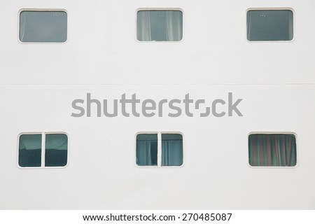 Cabin windows of a big white cruise ship, docked in port for maintenance, refill of supplies and sightseeing tour for passengers. Travel, hospitality, cruising business concept and background.  - stock photo