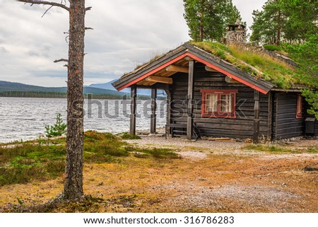 Cabin with turf roof with a lake in the background in Norway - stock photo