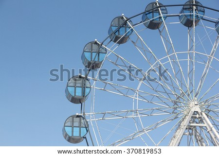 Cabins the ferris wheel against the blue sky - stock photo