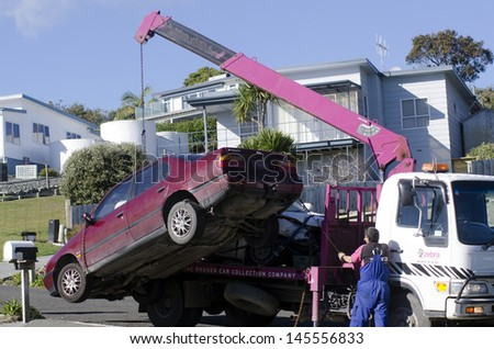 CABLE BAY,NZ - JULY 01:Man towing damaged car over a tow truck on July 01 2013.Many tow companies have the capability to store vehicles that have been wrecked or impounded by police agencies. - stock photo