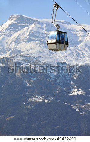 cable car carrying a passenger in the mountains - stock photo