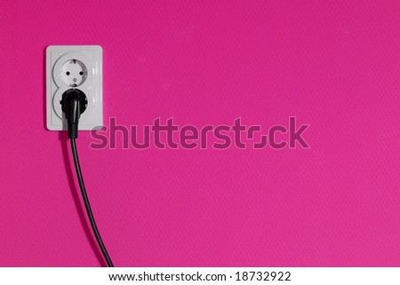 Cable connected into a power outlet on a pink wall - stock photo