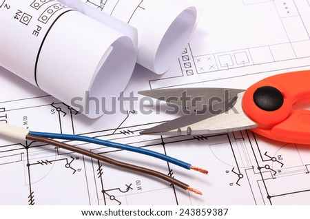 Cable cutter, electric wire and rolls of electrical diagrams lying on construction drawing of house, accessories for engineer jobs - stock photo