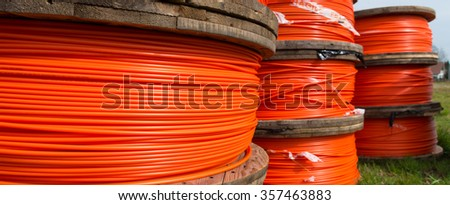 cable drums with orange fiber cable on a construction site - stock photo