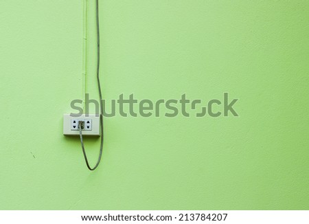 cable plugged in a white electric outlet mounted on green wall - stock photo