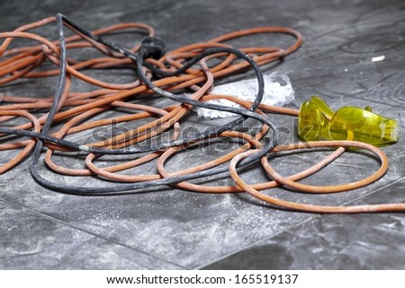 Cable power cords in a tangled mess on floor workplace - stock photo