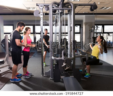 cable pulley system gym workout fitness people with personal trainer - stock photo