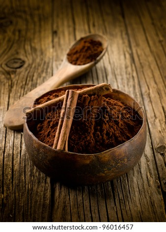 cacao powder with cinnamon on wood bowl - stock photo