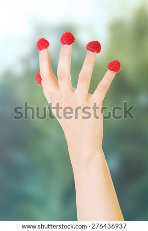 Cacuasian woman's hand with raspberries on fingers. - stock photo