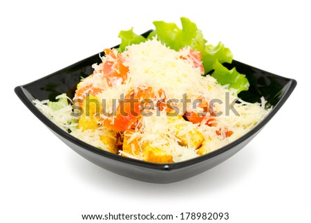 caesar salad in black bowl, over white background - stock photo