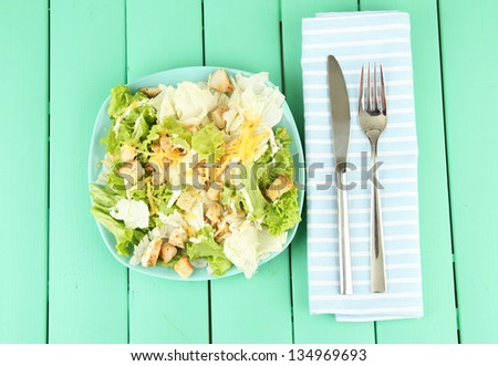 Caesar salad on blue plate, on color wooden background - stock photo