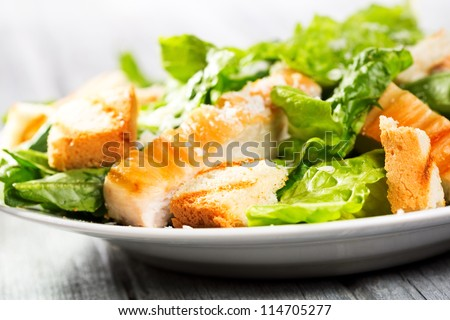 Caesar salad on wooden table - stock photo