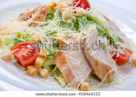 Caesar salad with chicken on white plate.Salad with grilled chicken breast, fresh lettuce and slices of cherry tomatoes, parmesan cheese and croutons of white bread on a white plate closeup.  - stock photo