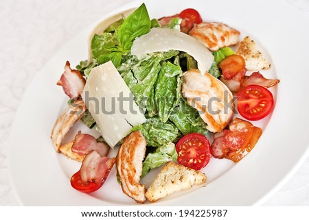 Caesar salad with chicken, spinach, cherry tomatoes, parmesan, bacon and croutons - stock photo