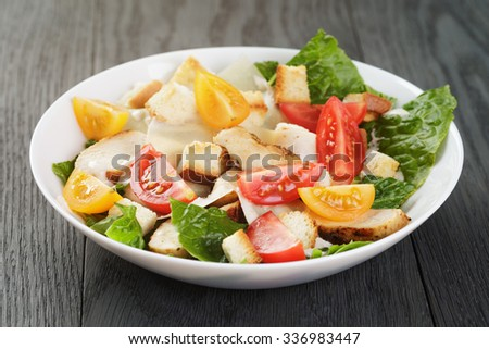 caesar salad with chiken fillet and different color tomatoes, wood table - stock photo