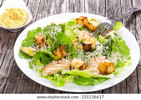 Caesar salad with cos lettuce, croutons and grilled chicken breast on the white dish on an old wooden table, rustic style, close-up - stock photo