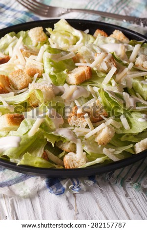 Caesar salad with croutons and parmesan close-up on a plate. vertical  - stock photo