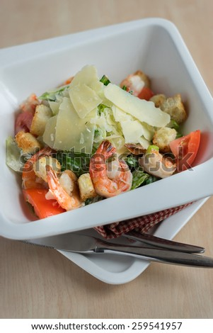 Caesar salad with cucumbers, tomatoes, cabbage, salad leaves, roasted shrimps and shaved parmesan cheese in a plate, selective focus - stock photo