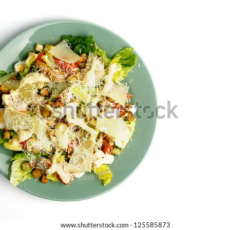 Caesar Salad with Grilled Chicken, Crouton, Romaine Lettuce, Sauce and Grated Parmesan Cheese closeup on Green Plate. Top View - stock photo