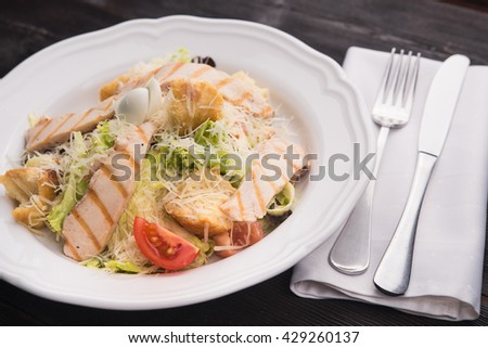 Caesar salad with grilled chicken in restaurant table - stock photo