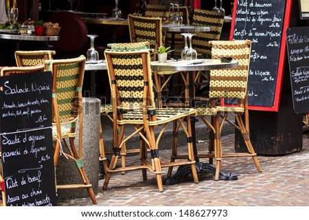 Cafe at rue Mouffetard in Paris - traditional wicker furniture and menu boards exposed on the pavement, Paris, France - stock photo